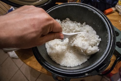 Turning the cooked ricer in the cooker before transferring it to a large bowl for mixing. The lid will shortly be replaced so it can continue to steam for a few minutes.
